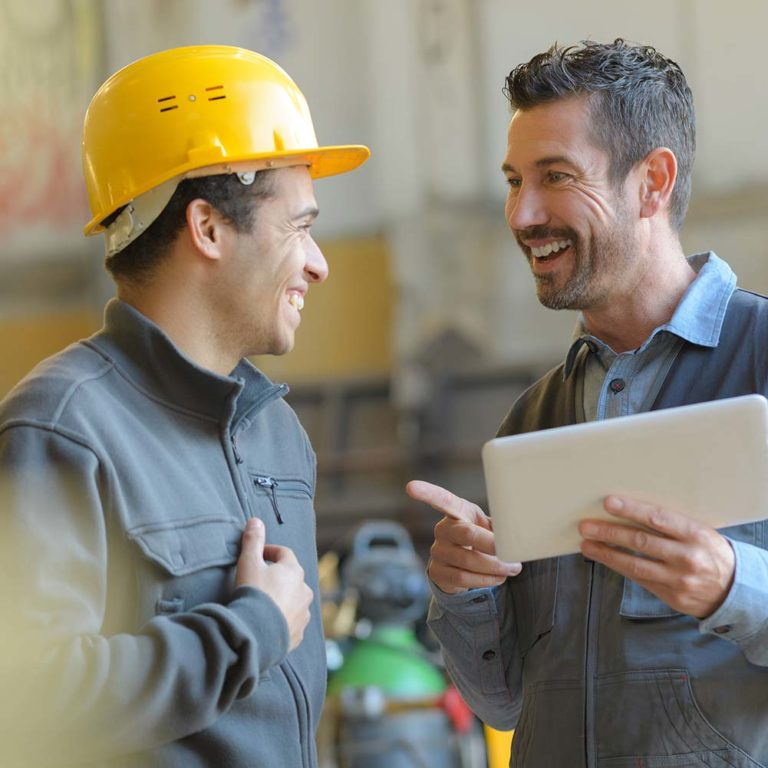 Two manufacturers smiling and holding an iPad